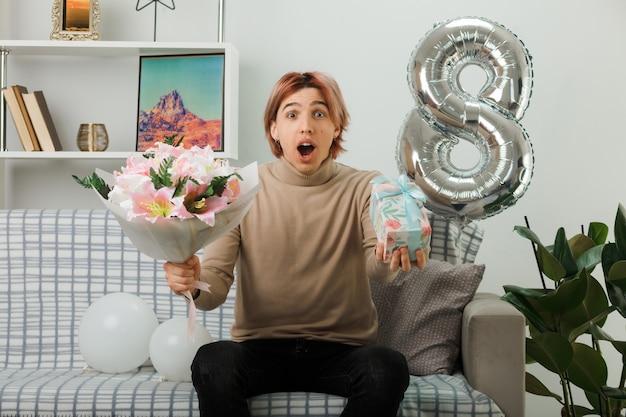 Przestraszony przystojny facet w szczęśliwy dzień kobiet trzymający prezent z bukietem, siedzący na kanapie w salonie