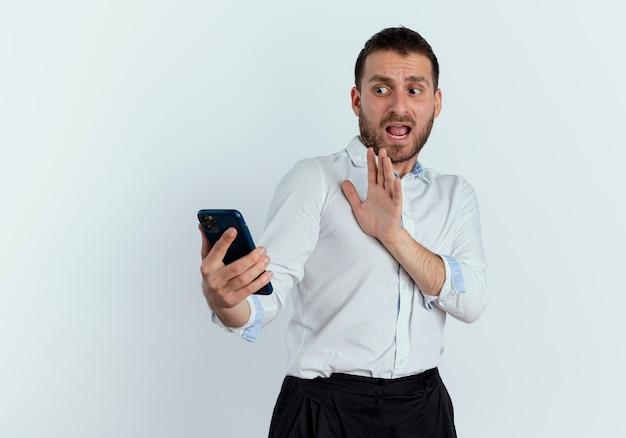 Przestraszony przystojny mężczyzna trzyma i patrzy na telefon z podniesioną ręką na białym tle na białej ścianie
