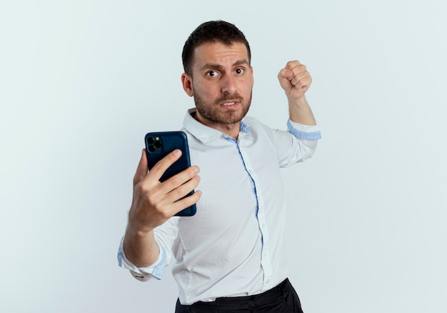 Przestraszony przystojny mężczyzna trzyma telefon i podnosi pięść gotowy do uderzenia na białym tle na białej ścianie