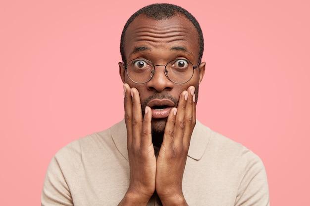 Przestraszony przystojny młody mężczyzna słyszy nagłe negatywne wieści, trzyma dłonie na policzkach, nosi okulary i zwykłe ubranie,