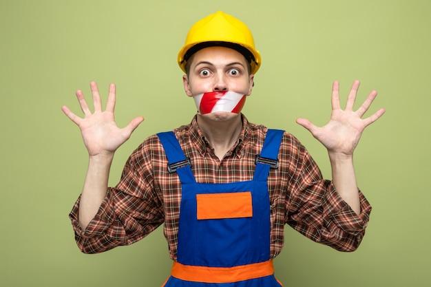 Przestraszony rozkładający ręce młody mężczyzna budowniczy noszący mundur zapieczętowane usta taśmą klejącą