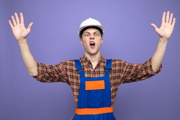 Przestraszony rozkładający ręce młody mężczyzna budowniczy ubrany w mundur