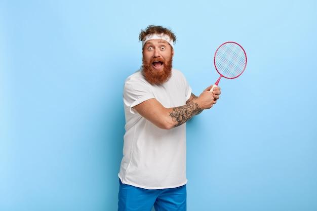 Przestraszony rudowłosy tenisista trzyma rakietę, pozując przy niebieskiej ścianie