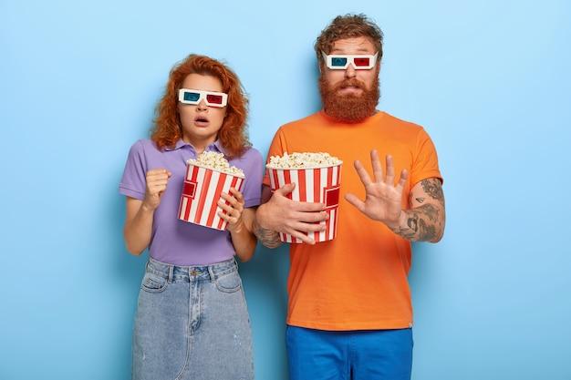 Przestraszony rudy chłopak i dziewczyna jedzą popcorn i oglądają horror