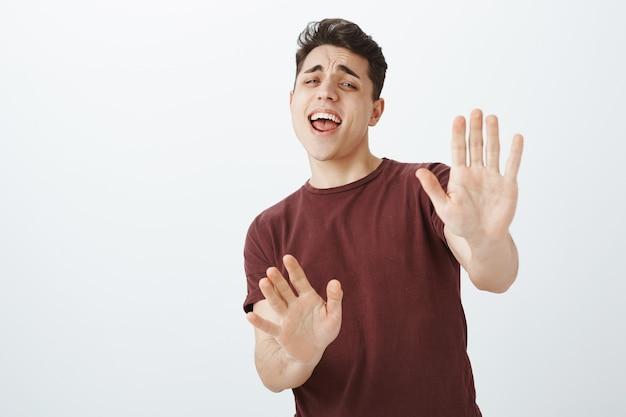 Przestraszony zabawny młody chłopak w czerwonej koszulce