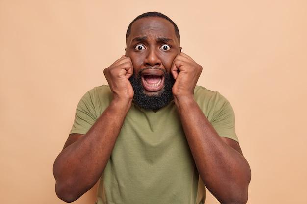 Przestraszony, zmartwiony mężczyzna trzyma ręce na twarzy, zaniepokojony, przestraszony, że coś ma wyłupiaste oczy, opadła szczęka, nosi luźną koszulkę odizolowaną na beżowej ścianie