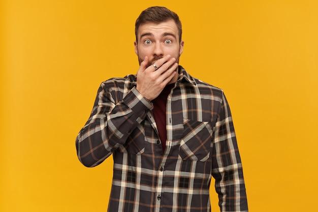 Przestraszony, zszokowany młody człowiek w kraciastej koszuli z brodą zakrył usta ręką i wygląda na oszołomionego na żółtej ścianie