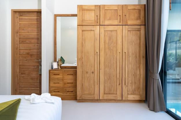 Przestronna i nowoczesna sypialnia z drewnianą szafą