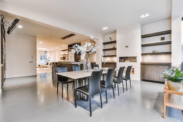 Przestronna jadalnia w stylu minimalistycznym ze stołem i krzesłami w nowoczesnym apartamencie z drewnianą podłogą