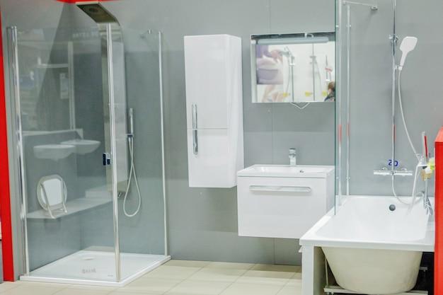 Przestronna łazienka w odcieniach szarości z wolnostojącą wanną, kabiną prysznicową i podwójną umywalką.
