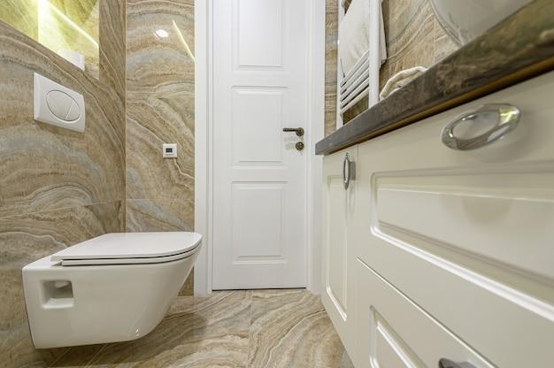 Przestronna luksusowa łazienka z białą toaletą wodną, szafką i beżowymi marmurowymi kafelkami