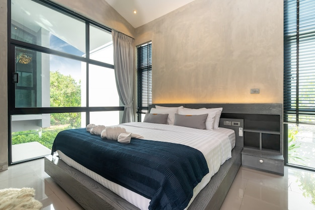 Przestronna nowoczesna sypialnia na poddaszu z niebieską pościelą