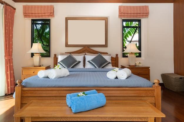 Przestronna sypialnia z niebieskim prześcieradłem i drewnianym drelichiem