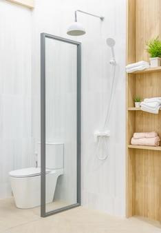Przestronne i jasne wnętrze nowoczesnej łazienki z białymi ścianami, kabina prysznicowa ze szklaną ścianą