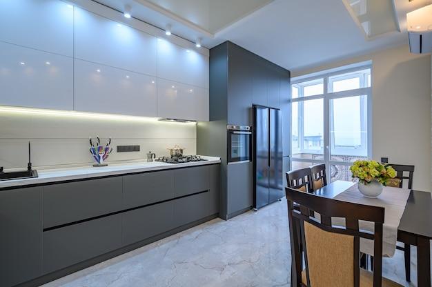 Przestronne luksusowe białe i ciemnoszare nowoczesne wnętrze kuchni ze stołem jadalnym