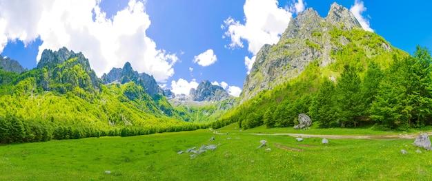 Przestronne malownicze łąki wśród ogromnych gór.