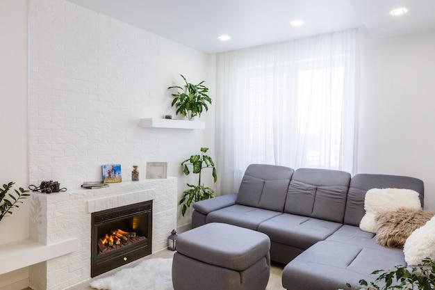 Przestronne wnętrze willi z efektem cementowej ściany, kominkiem i telewizorem