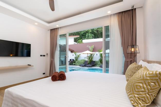 Przestronny dostęp do basenu z sypialnią i przesuwanymi drzwiami z widokiem na ogród z leżakiem i parasolem