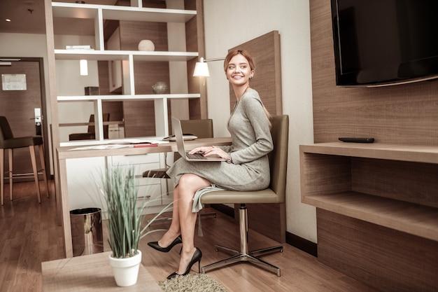 Przestronny pokój hotelowy. promieniejąca atrakcyjna młoda bizneswoman pracująca w przytulnym, przestronnym pokoju hotelowym
