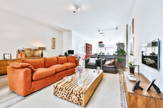 Przestronny pokój w domu z sofą i fotelami przy telewizorze oraz designerskim drewnianym stołem z kwiatowym wazonem
