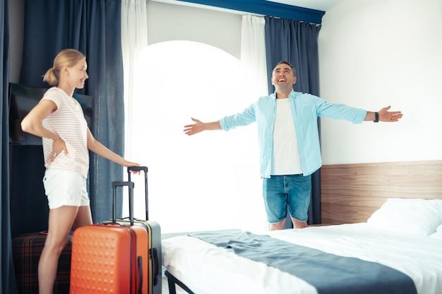 Przestronny pokój. wesoły mąż i żona stoją w pokoju hotelowym z rozpakowanymi walizkami podróżnymi, szczęśliwi na wakacjach.