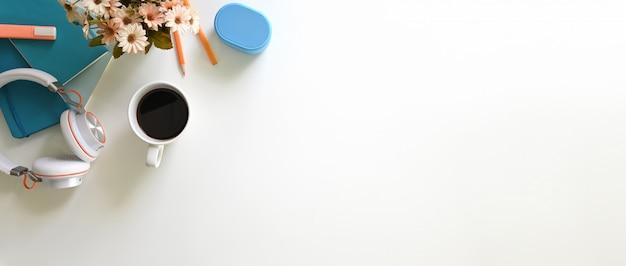 Przestrzeń do pracy otaczają słuchawki, kawa, doniczka i akcesoria.
