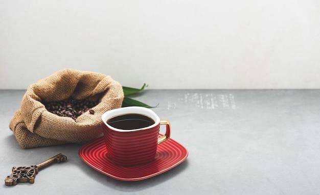 Przestrzeń kawa w czerwonej filiżance i ziarno kawy z liśćmi