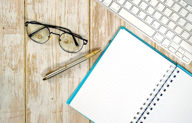 Przestrzeń robocza do pracy z drewnianym białym stołem z okularami na klawiaturę i materiałami eksploatacyjnymi płaska kompozycja świecka