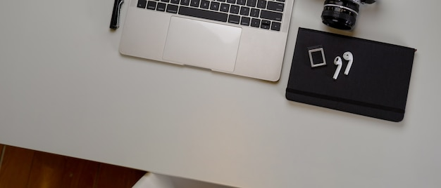 Przestrzeń robocza nowoczesnego fotografa z makietą laptopa, aparatu, książki harmonogramu i miejsca kopiowania