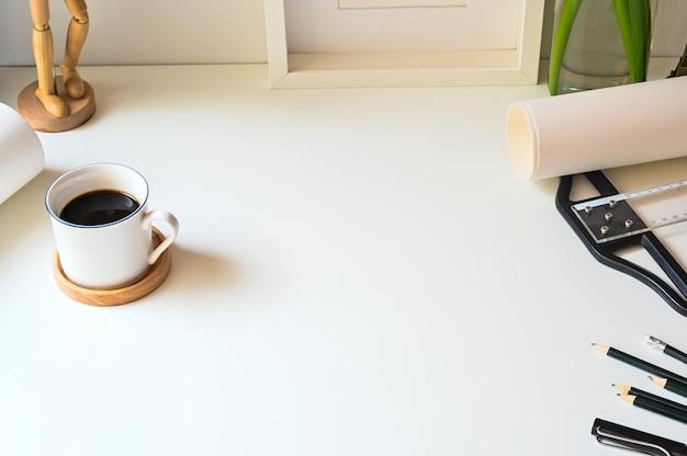 Przestrzeń robocza z ołówkiem, linijką, ramką na zdjęcia i kawą.