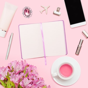 Przestrzeń robocza z pamiętnikiem, długopisem, smartfonem, pomadką, alstremerią, filiżanką herbaty, kosmetykami