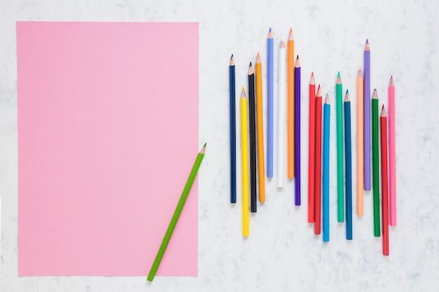Przestrzeń robocza z pustym kawałkiem papieru i ołówkami