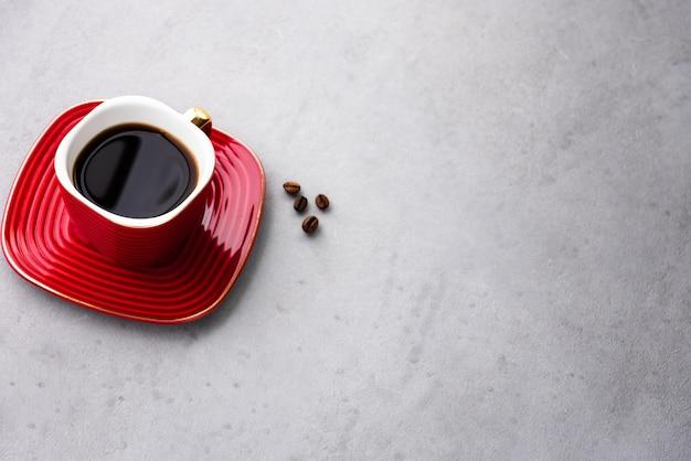 Przestrzeń rocznika kawy w czerwony kubek i jedzenie ziaren kawy