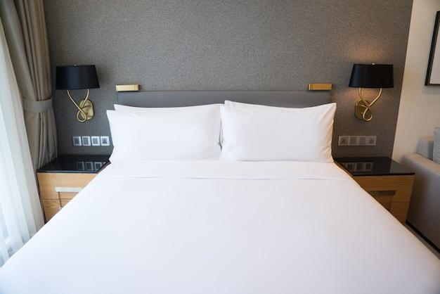Przestrzeń sypialni w mieszkaniu z szarą ścianą, dwiema lampami i szafkami.