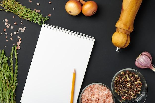 Przestrzenie, przyprawy i czysty zeszyt z ołówkiem. makieta papieru zeszyt do koncepcji przyjęcia żywności, menu lub blog żywności. widok z góry