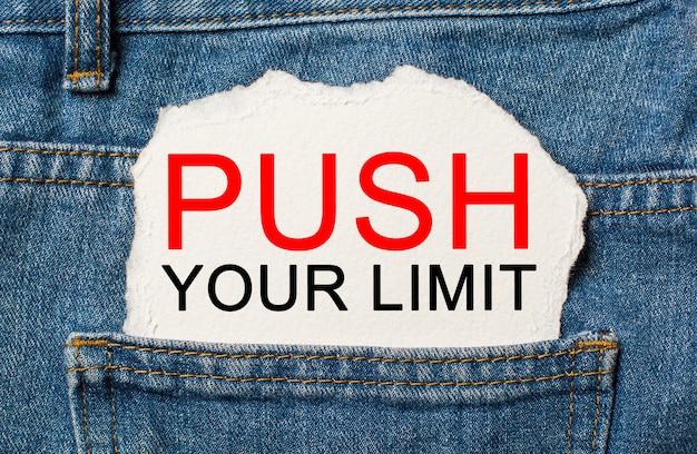 Przesuń swój limit na rozdartym tle papieru na koncepcji dżinsów i finansów