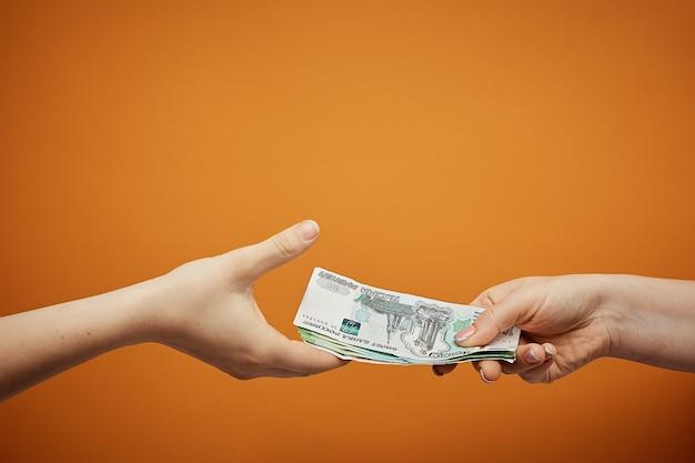 Przesyłaj pieniądze sobie nawzajem, dwiema rękami i gotówką na pomarańczowo.