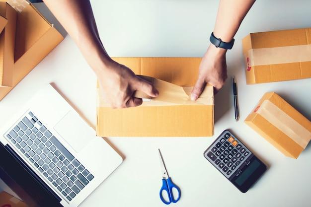 Przesyłka sprzedaż online. mężczyzna dostawa pracownika i działające pudełko do pakowania, właściciel firmy sprawdza zamówienie w celu potwierdzenia przed wysłaniem klienta pocztą. widok z góry