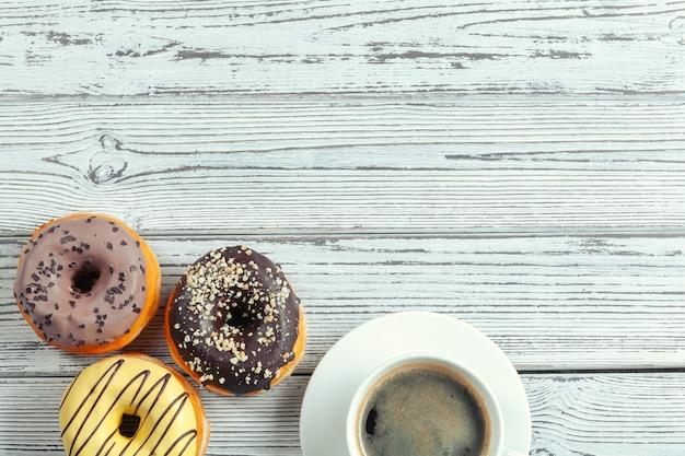 Przeszklone pączki na drewnianej powierzchni z filiżanką kawy