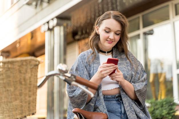 Przeszukuje telefon komórkowy całkiem młoda kobieta