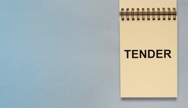 Przetarg słowo na papierze notatnika na niebieskoszarym tle z copyspace na tekst baner biznesowy z ko...