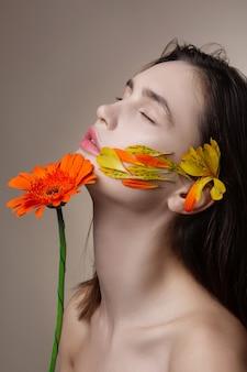 Przetargowy model. delikatny czarnowłosy model z płatkami na twarzy i kwiatem w dłoniach zamykających oczy