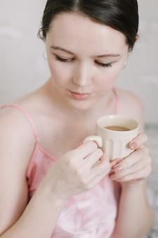 Przetargowy portret młodej kobiety piękne, trzymając filiżankę kawy w łóżku w domu