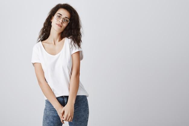 Przetargu atrakcyjna kobieta w okularach patrząc na szarej ścianie