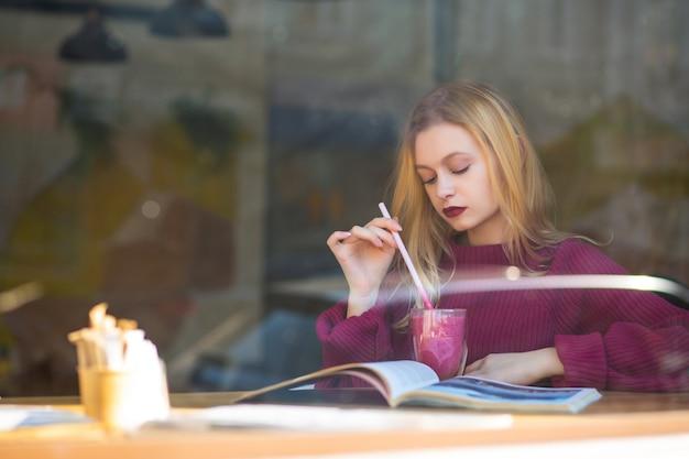 Przetargu młoda kobieta spędza czas w restauracji przy filiżance kawy. strzał przez szybę w oknie. miejsce na tekst