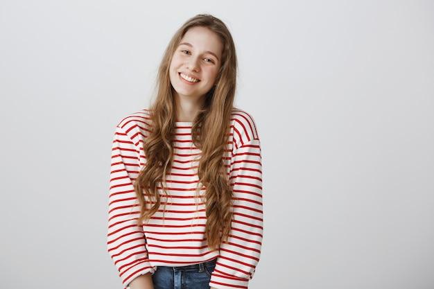 Przetargu piękna dziewczyna uśmiecha się szczęśliwy na szarej ścianie