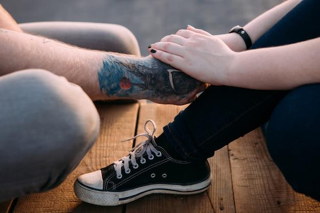 Przetargu romantyczna oprawa. para trzymając się za ręce. nierozpoznawalni ludzie komunikują się ze sobą, koncentrując się na pierwszym planie, miejskim tle. delikatny dotyk, koncepcja czułości