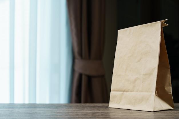 Przetwarza brown papierową torbę na drewnianym stole.