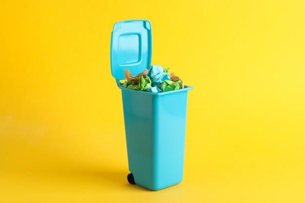 Przetwarza kosz z śmieci na żółtym tle, przestrzeń dla teksta