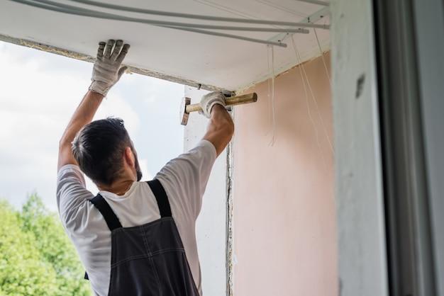 Przetwarzać męskiego pracownika naprawiania okno w domu, zamyka up
